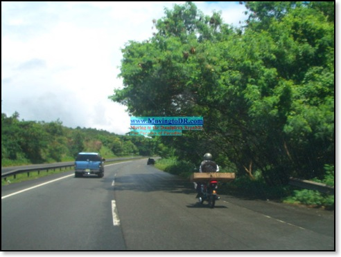 Dominican Republic picture- Moto Driver takes to highway with a five foot long box